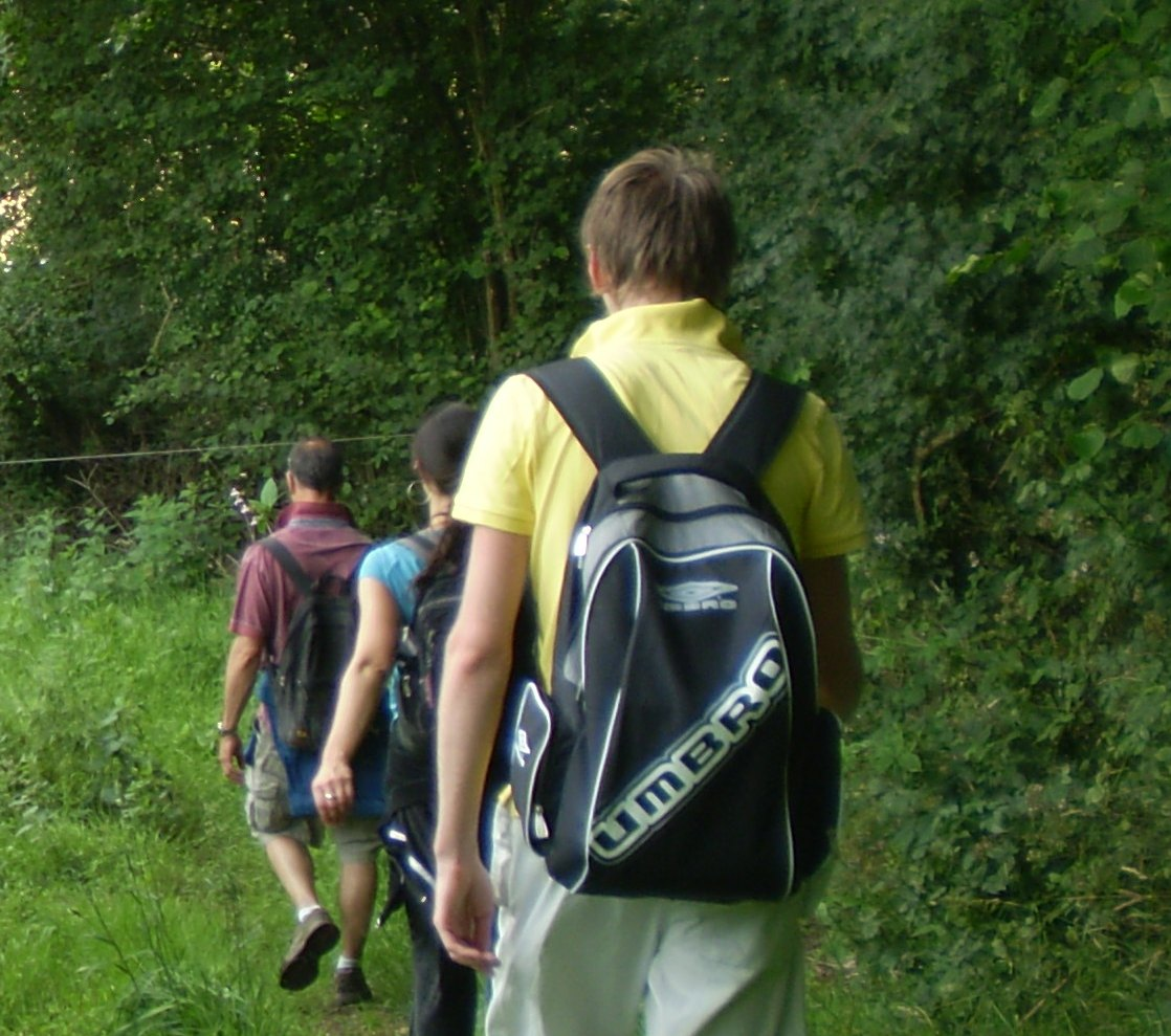 A family walking with rucksacks on their backs