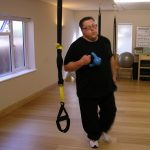Richie jogs around the studio carrying kettlebells